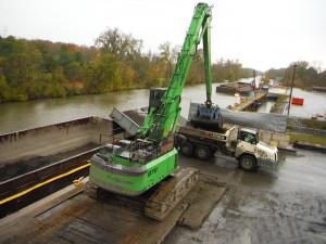 Two SENNEBOGEN 870 material handlers unload 6 to 8 barges of dredged sediment from the Hudson River every day.