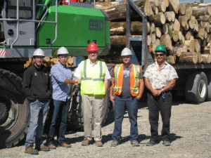 Strongco's Territory Manager Allan Lindsay, centre, congratulates Vincent Caron on delivery of the SENNEBOGEN 830 M-T, joined by Caron's Groupe Savoie team: Service Manager Tobby Leclair far left and, to the right, Yard Manager Tommy Lefebvre and Operator Mario Levesque.