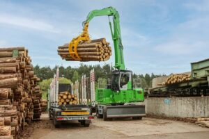A 735 E with timber grapple unloading a truck trailer.
